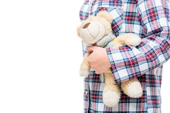 Favorit- nallebjörn i händerna av en vuxen kvinna i pyjamas arkivfoton