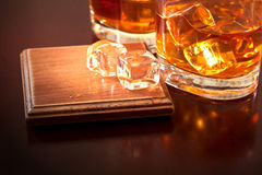 Favorite brand of whiskey. A glass of whiskey with ice cubes on the table Royalty Free Stock Photo