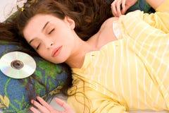 Favorite CD. Beautiful young woman sleeping beside favorite cd Stock Photography