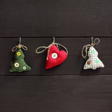Favorite Christmas trees. Flat layout of festive toys on a dark wooden background Stock Photos