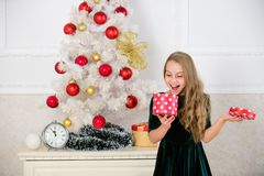 Favorite day of the year. Time to open christmas gifts. Opening christmas presents. Dreams come true. Surprise concept. Kid girl near christmas tree hold gift royalty free stock images