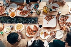 Favorite food. Close up top view of young people eating pizza while having a dinner party indoors royalty free stock images