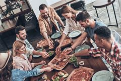 Favorite food. Top view of young people in casual clothing picking pizza and smiling while having a dinner party royalty free stock photography