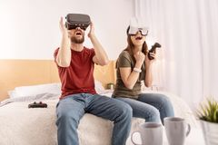Excited vigorous couple emulating in VR headsets. Favorite game. Young pretty pleasant couple relaxing in bedroom while playing in VR glasses and opening mouths Stock Image