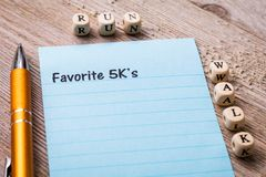 Favorite 5K`s run walk concept on notebook and wooden board. 5K run walk concept on notebook and wooden board Royalty Free Stock Photo