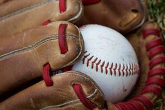 Favorite past-time. Close up of baseball and glove with unique red lacing Stock Photography