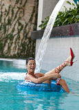Favorite red shoes. Smiling female at the edge of a swimming pool Stock Photo