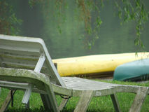 Favorite Spot. Lakeside lounge chair with two canoes in background stock photography