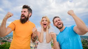 Favorite team won competition. Woman and men look successful celebrate victory sky background. Threesome stand happy. With raised fists. We are winners royalty free stock photos