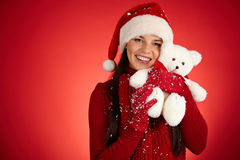 Favorite toy. Cute girl in Santa cap with white teddy bear posing in isolation stock images