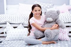 Favorite toy. Girl child sit on bed hug teddy bear in her bedroom. Kid prepare to go to bed. Pleasant time in cozy. Bedroom. Girl kid long hair cute pajamas stock image
