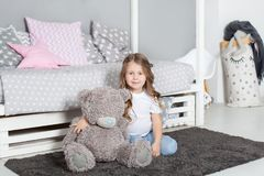 Favorite toy. Girl child sit on bed hug teddy bear in her bedroom. Kid prepare to go to bed. Pleasant time in cozy bedroom. Girl k stock photos