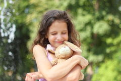Favorite toy. Portrait of a girl with a favorite toy on the background of nature. soft focus. bokeh Stock Images