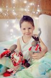 Favorite toys. The boy woke up and sat on the bed with toy reindeer Royalty Free Stock Photography