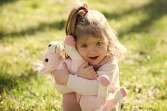 Favorite toys. Baby girl hug soft horse toy on sunny day. On green grass. Cuddling, love, friend. Playing, game concept. Child, childhood, playground Stock Photo