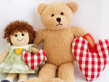 Favorite toys. Little girl's toys - a doll and a teddy bear with soft stuffed hearts Royalty Free Stock Photos