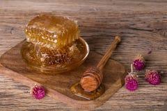 Favos de mel e colher do mel em uma placa de madeira e em uma tabela Fotos de Stock