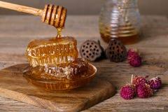 Favos de mel e colher do mel em uma placa de madeira e em uma tabela fotografia de stock