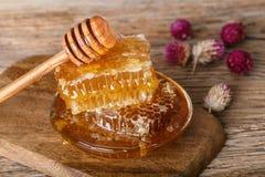 Favos de mel e colher do mel em uma placa de madeira e em uma tabela Foto de Stock