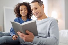 Inspired father reading a book for his daughter. Favourite activity. Good-looking alert dark-haired reading a book and the girl sitting near him and smiling Royalty Free Stock Image
