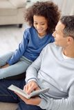 Alert father reading a book for his daughter. Favourite book. Pretty happy curly-haired girl smiling and sitting near her father and her daddy holding a book Royalty Free Stock Image