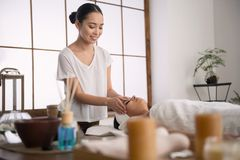 Cheerful young masseuse smiling. Favourite job. Cheerful young masseuse smiling to her client while enjoying her job Stock Photos