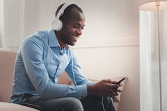 Happy positive man choosing the song royalty free stock image