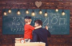 Favourite teacher concept. Teacher with beard, father teaches little son in classroom, chalkboard on background. Boy. Child in graduate cap listening teacher royalty free stock image
