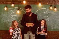 Favourite teacher concept. Man with beard and schoolgirls with school attributes. Teacher and girls pupils in classroom. Chalkboard on background. Children and stock photography