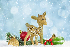 Fawn with fir branch and holly leaves Stock Photos