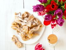 Faworki - Traditional Polish cookies served at Fat Thursday. Cookies and tulip bouquet on white wooden background Stock Images