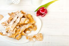 Faworki - Traditional Polish cookies served at Fat Thursday. Cookies and tulip bouquet on white wooden background Royalty Free Stock Photography