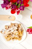 Faworki - Traditional Polish cookies served at Fat Thursday. Cookies and tulip bouquet on white wooden background Royalty Free Stock Photos