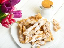Faworki - Traditional Polish cookies served at Fat Thursday. Cookies and tulip bouquet on white wooden background Stock Photography