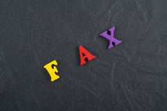 FAX word on black board background composed from colorful abc alphabet block wooden letters, copy space for ad text stock images