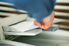 Faxing or copying something. A man (only hand to be seen) faxing a pile of paper or taking it out of a printer Stock Photo