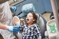 Faz crian?as querer escovar Crian?a no escrit?rio dental O dentista explica a seu paciente como escovar os dentes imagens de stock