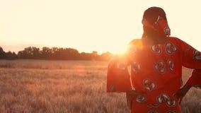 Fazendeiro africano da mulher na roupa tradicional que está em um campo das colheitas, trigo ou cevada, em África no por do sol o filme