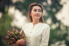 Fazendeiro bonito da jovem mulher que recolhe lótus foto de stock