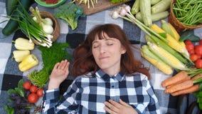 Fazendeiro bonito da mulher do retrato com os olhos fechados que encontram-se em uma manta entre vegetais orgânicos frescos Vista vídeos de arquivo