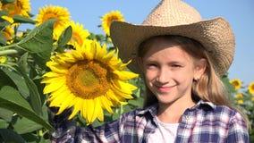 Fazendeiro Child no campo do girassol, jogo feliz da menina exterior na natureza 4K video estoque