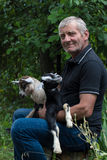 Fazendeiro cinzento-de cabelo de sorriso que guarda duas cabras do bebê em seus braços Fotos de Stock