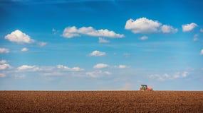 Fazendeiro com o trator que semeia colheitas no campo Foto de Stock Royalty Free