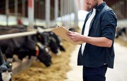 Fazendeiro com prancheta e vacas no estábulo na exploração agrícola imagens de stock royalty free