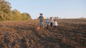 Fazendeiro com suas quatro crianças que vão no campo de exploração agrícola para o trabalho junto video estoque