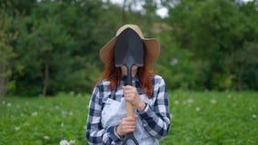 Fazendeiro da jovem mulher que guarda uma pá e que sorri no jardim filme