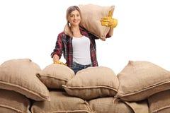 Fazendeiro fêmea atrás de uma pilha de sacos de serapilheira fotos de stock royalty free
