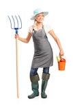 Fazendeiro fêmea que prende um pitchfork e uma cubeta Fotos de Stock Royalty Free