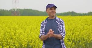 Fazendeiro feliz With Hands Clasped que está no campo da colza vídeos de arquivo