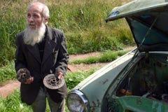 fazendeiro idoso Cinzento-farpado do camponês, reparos antiquados do carro Imagem de Stock
